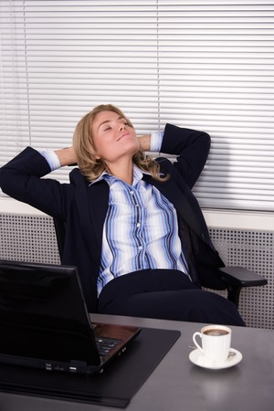 Beautiful woman relaxing in office with a laptop photo