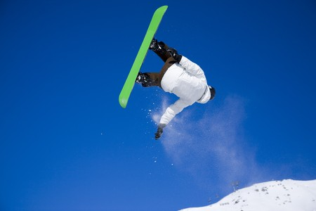 air jump: snowboarder taking big air jump with bright blue sky Stock Photo