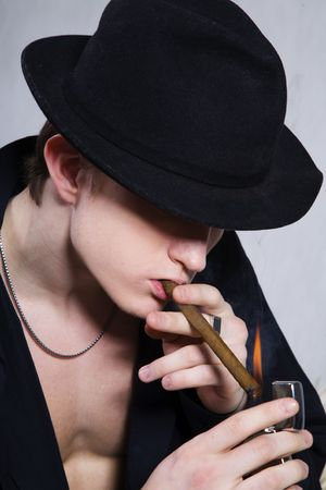 portrait of a guy smoking a cigar on gray background