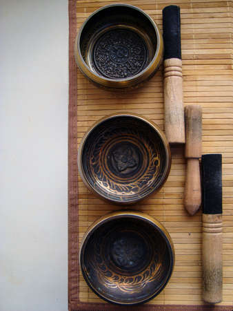 tibetan singing bowl: three Tibetan bowls with sticks on the background of straw Mat