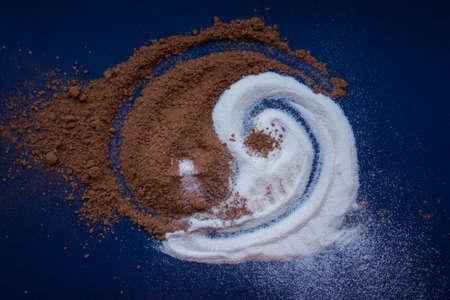 er Yin und Yang von Milchpulver und Kakaopulver auf einem blauen Hintergrund