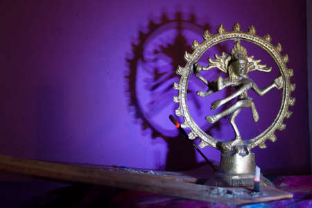 esoterismo: statue of Lord Shiva with incense on violet background at night Foto de archivo