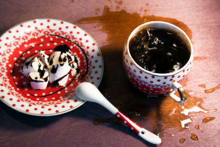 watered: ceramic Cup polka dot spilled around coffeetea and spray with spoon and saucer with cream watered with chocolate on wooden background