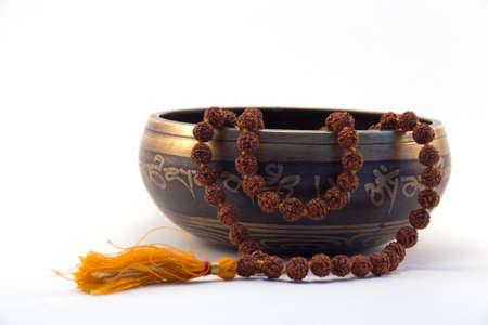 singing bowl: Tibetan singing bowl with engraved mantra and rudraksa side view on white background 2