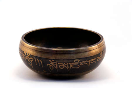 bronze bowl: Tibetan singing bowl engraved with the mantra side view on white background