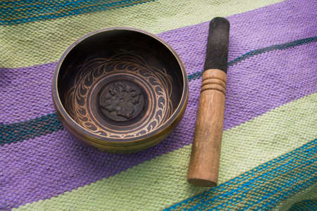 singing bowl: Tibetan singing bowl with stick on the background of linen Mat Stock Photo