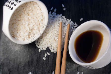 soy sauce: rice, soy sauce and chopsticks on a black background Stock Photo