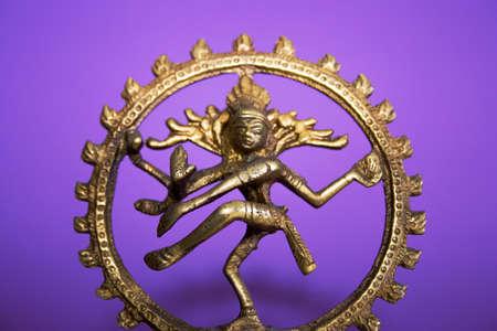 spiritualism: bronze statuette of Shiva Nataraja on a purple background