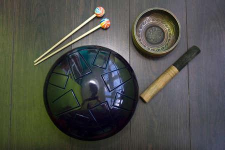 tibetan singing bowl: hangdrum and Tibetan singing bowl on a dark wooden floor,