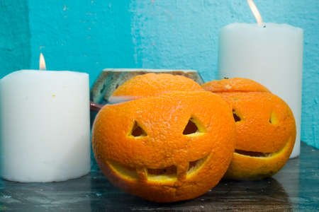 oranges with carved faces with white candles and a clay pot on a blue background with the autumn Halloween theme