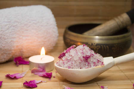 homemade body scrub from sea salt and rose petals and peony, Tibetan bowl,candle,pink towel on a straw Mat. Spa concept Stock Photo