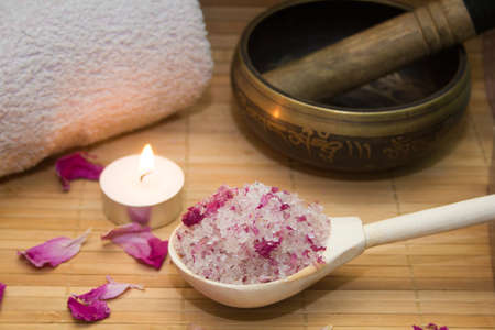 singing bowl massage: homemade body scrub from sea salt and rose petals and peony, Tibetan bowl,candle,pink towel on a straw Mat. Spa concept Stock Photo