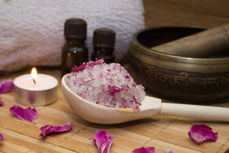 singing bowl massage: homemade body scrub from sea salt and rose petals and peony, Tibetan bowl,candle,pink towel and aroma oil  on a straw Mat. Spa concept Stock Photo