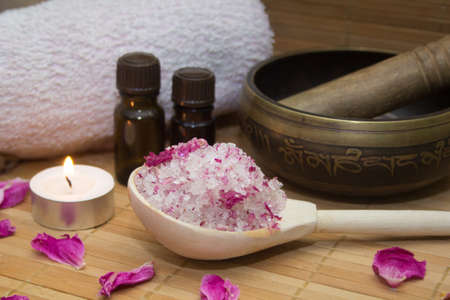 aroma bowl: homemade body scrub from sea salt and rose petals and peony, Tibetan bowl,candle,pink towel and aroma oil  on a straw Mat. Spa concept Stock Photo