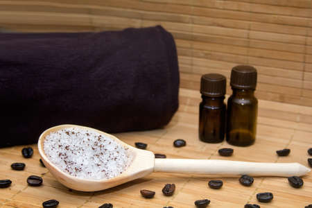 singing bowl massage: Spa concept.Coffee scrub, coffee beans, towel, aroma oil, candle on straw mat  background