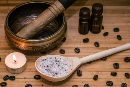singing bowl massage: Spa concept.Coffee scrub, coffee beans, singing bowl, aroma oil, candle on straw mat  background