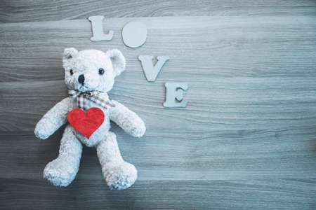 Teddy bear, LOVE letters, heart on wooden background. Place for text. The concept to St. Valentine.