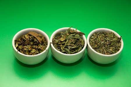 lemongrass tea: green tea different grinding in white bowls on green background