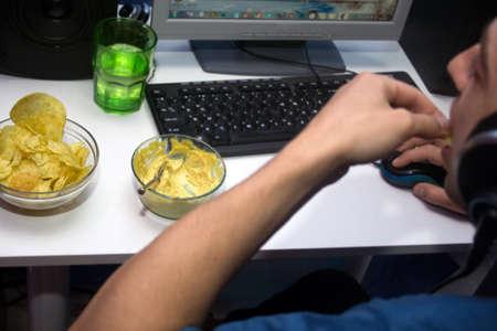 sedentario: El hombre usando una computadora y comer comida rápida. Concepto de estilo de vida sedentario y los malos hábitos alimenticios