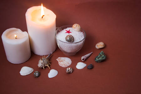 swimming candles: Spa concept. Seashells , candles and  sea salt  on brown background Stock Photo