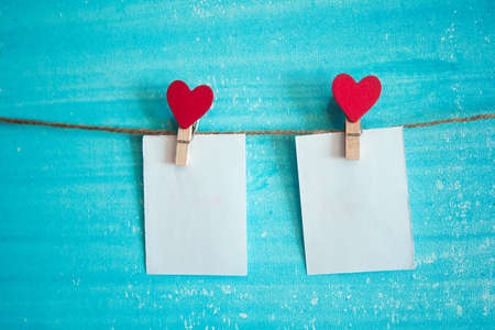 white sheet of paper on the clothespin with hearts Stock Photo