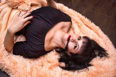 femme fatale: young sexy brunette lies on a beige blanket on the floor.