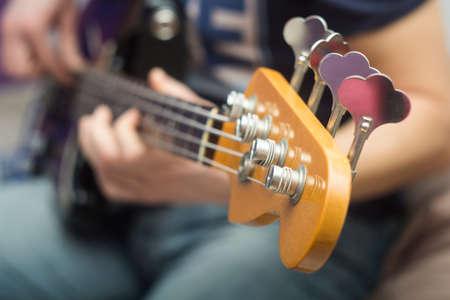 acoustics: young man plays bass guitar