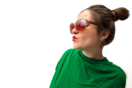 young girl in sunglasses and a green shirt on a white background