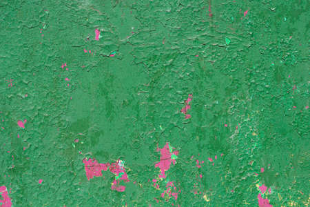 texture of the wall painted a rich green with splashes of pink layer underneath
