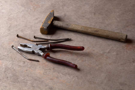 rusty old nails ,hammer and pliers on wooden background Stock Photo