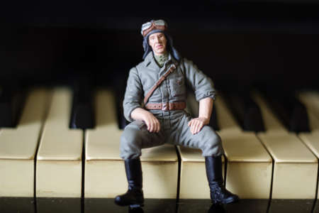 plastic soldier: toy military man sits on the keys of a piano