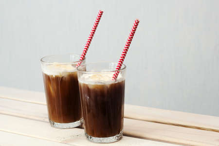 two glasses of cold coffee with ice cream with a cocktail straw on a table against white wall Stock Photo