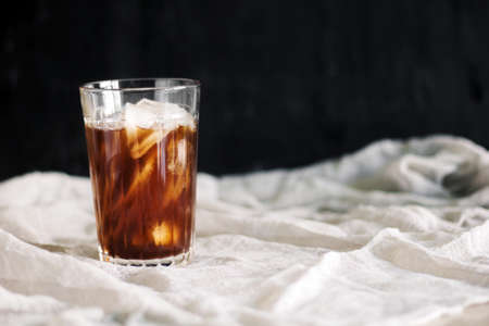 a glass of black iced coffee