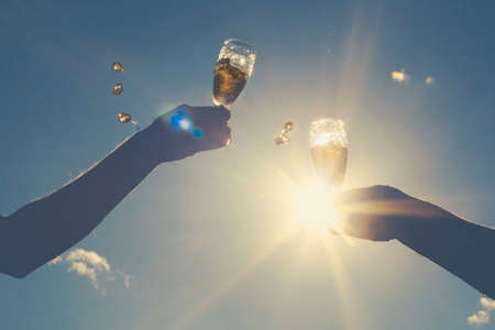 Hands of man and woman clink wineglasses of sparkling white wine on  sky and sun. retro toned Stock Photo