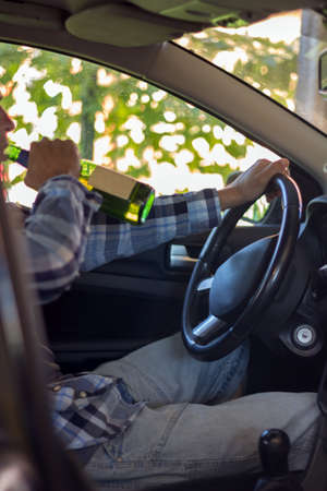habbit: Young man drinking beer while driving. the problem of alcoholism and drunk driving.