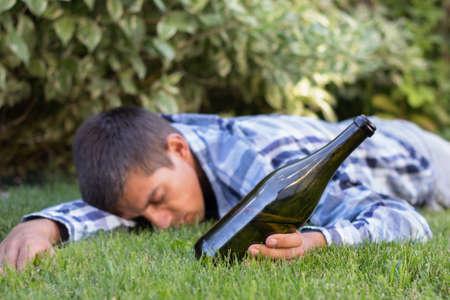 Un homme ivre qui dort dans le parc après la fête. Le problème de l'alcoolisme.