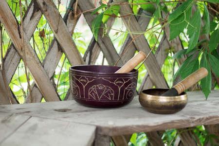 Wo Tibetaanse zangbakken met stokken op een houten bank in een tuin