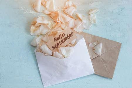 バラの花びらと言う「こんにちは 9 月」メモをフェージングと 2 つの封筒。トーンダウン。