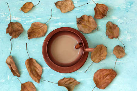 a warming mug of coffee with milk and cinnamon  among the autumn leaves