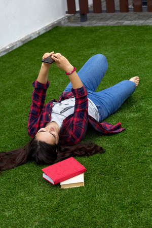 a young girl makes a selfie lying on the grass.