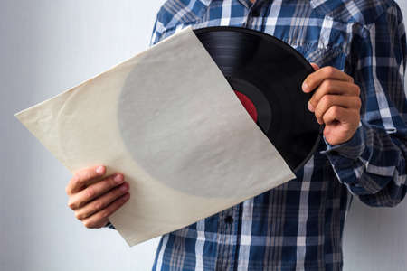 man holds white blank vinyl cover and vinyl record in hands