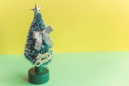 miniature Christmas tree on yellow and green  background, place for text