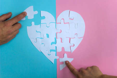male and female hands collect puzzle heart on pink and blue background Stock Photo