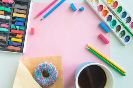 top view of working place of the artist with the drawing tools, a donut and coffee, and a blank sheet of paper mock up Zdjęcie Seryjne