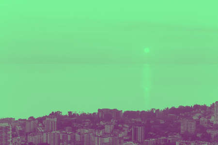 city view with buildings,sea and sky toned in green and violet Stock Photo