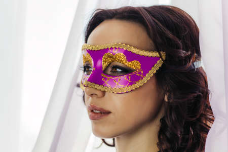 beautiful young woman in pink and golden mask Stock Photo