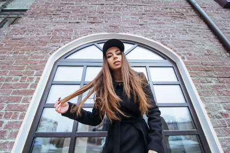 bottom view stylish beutiful girl in a black coat and black cap urban portrait