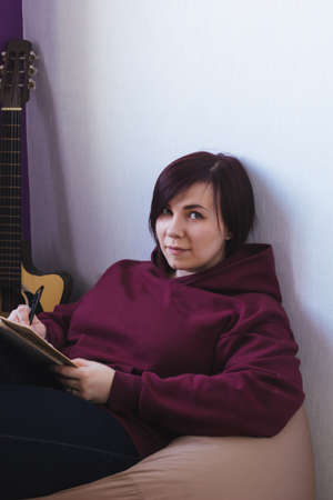 young creative woman sitting on a chair and compose a new song 스톡 콘텐츠