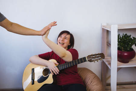 young woman with a guitar gives five men from her music band Banco de Imagens