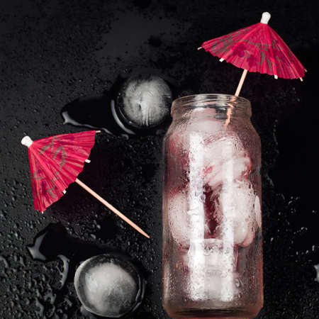 top view glass jar with red cocktail and ice,decorated with umbrella Stock Photo